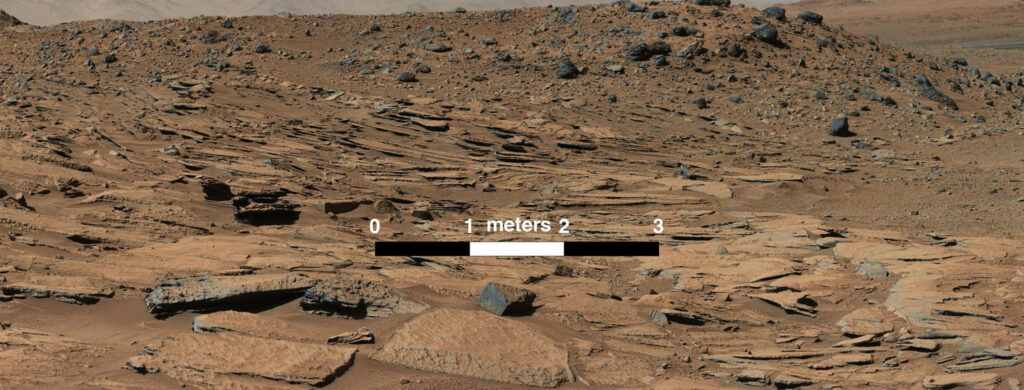 """This image taken by the Mast Camera (Mastcam) on NASA's Curiosity Mars rover just north of the """"Kimberley"""" waypoint shows beds of sandstone inclined to the southwest toward Mount Sharp and away from the Gale Crater rim. The inclination of the beds indicates build-out of sediment toward Mount Sharp. These inclined beds are interpreted as the deposits of small deltas fed by rivers flowing down from the crater rim to the north and building out into a lake to the south, where Mount Sharp is now."""