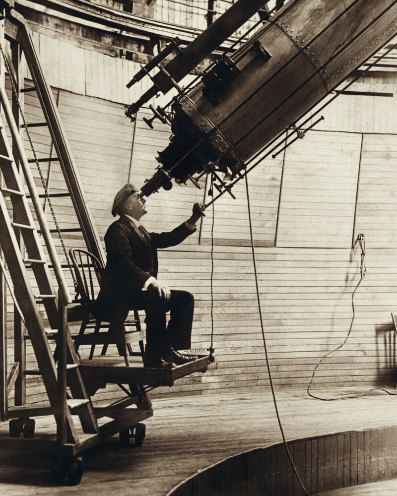 American astronomer Percival Lowell using a large telescope to observe Venus.