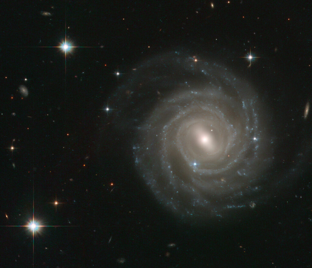 The galaxy captured in this image, called UGC 12158, certainly isn't camera-shy: this spiral stunner is posing face-on to the NASA/ESA Hubble Space Telescope's Advanced Camera for Surveys, revealing its structure in fine detail. UGC 12158 is an excellent example of a barred spiral galaxy in the Hubble sequence — a scheme used to categorise galaxies based on their shapes. Barred spirals, as the name suggest, feature spectacular swirling arms of stars that emanate from a bar-shaped centre. Such bar structures are common, being found in about two thirds of spiral galaxies, and are thought to act as funnels, guiding gas to their galactic centres where it accumulates to form newborn stars. These aren't permanent structures: astronomers think that they slowly disperse over time, so that the galaxies eventually evolve into regular spirals. The appearance of a galaxy changes little over millions of years, but this image also contains a short-lived and brilliant interloper — the bright blue star just to the lower left of the centre of the galaxy is very different from the several foreground stars seen in the image. It is in fact a supernova inside UGC 12158 and much further away than the Milky Way stars in the field — at a distance of about 400 million light-years! This stellar explosion, called SN 2004ef, was first spotted by two British amateur astronomers in September 2004 and the Hubble data shown here form part of the follow-up observations. This picture was created from images taken with the Wide Field Channel of Hubble's Advanced Camera for Surveys. Images through blue (F475W, coloured blue), yellow (F606W, coloured green) and red (F814W, coloured red) as well as a filter that isolates the light from glowing hydrogen (F658W, also coloured red) have been included. The exposure times were 1160 s, 700 s, 700 s and 1200 s respectively. The field of view is about 2.3 arcminutes across.