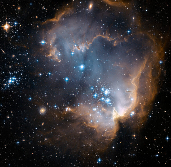 This image depicts bright blue newly formed stars that are blowing a cavity in the centre of a fascinating star-forming region known as N90. The high energy radiation blazing out from the hot young stars in N90 is eroding the outer portions of the nebula from the inside, as the diffuse outer reaches of the nebula prevent the energetic outflows from streaming away from the cluster directly. Because N90 is located far from the central body of the Small Magellanic Cloud, numerous background galaxies in this picture can be seen, delivering a grand backdrop for the stellar newcomers. The dust in the region gives these distant galaxies a reddish-brown tint.
